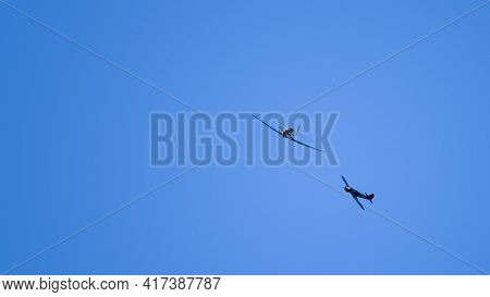Two Single-propeller Aircraft Performing High Aerobatics Maneuvers High In The Blue Sky At An Airsho