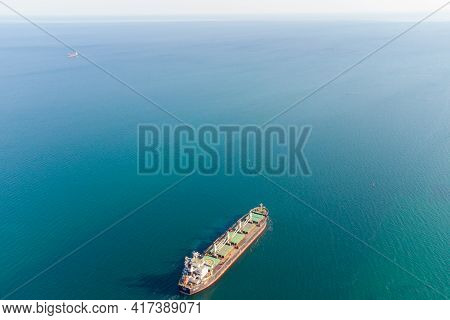The Dry Cargo Vessel Enters The Port With The Help Of Tugs. Photo From A Helicopter. Bird's-eye View