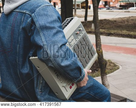 A Hip Hop Beatmaker In The Park Holds An Old-school ' 90s Drum Machine In His Hands . Retro Digital