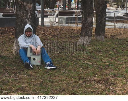 A Hip-hop Beatmaker Sits On The Grass In A Park Under A Tree Holding An Old-fashioned ' 90s Drum Mac