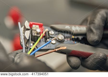 Wire Strippers. The Electrician Cleans The Protective Insulation From The Wire Using A Wire Stripper