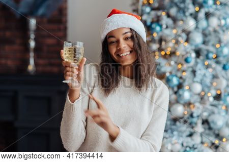 African American Woman With Glass Of Champagne At Home.