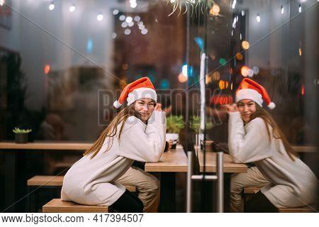 Girl Wearing Santa Claus Hat Sitting In Coffee Shop