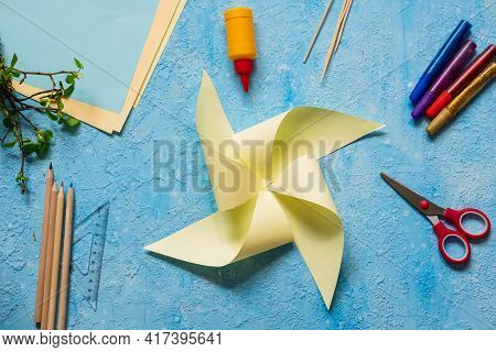 Step-by-step Making Of A Paper Weather Vane By A Child On A Blue Concrete Background. Children's Cre