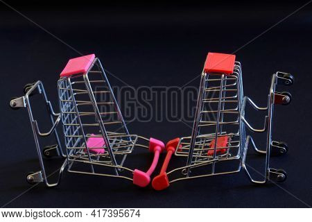 Upside Down And Overturned Empty Shopping Carts From The Supermarket On A Black Background. The Conc