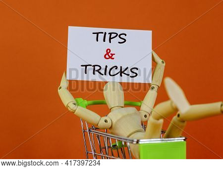 Tips And Tricks Symbol. White Paper. Words 'tips And Tricks'. Miniature Shopcart, Wooden Human. Beau