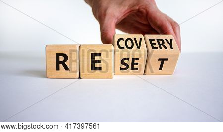 Recovery And Reset Symbol. Businessman Turns Cubes And Changes The Word 'recovery' To 'reset'. Beaut