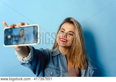 Portrait Of A Happy Young Girl With Glitter On Her Cheeks Taking A Selfie, Isolated On Blue Backgrou