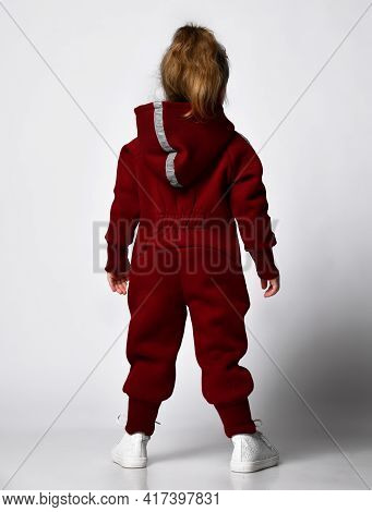 Rear View Of Little Preschooler Girl Wearing Warm Tracksuit Sportswear With Hood And White Trainers
