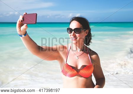 Smiling Young Adult European Woman In Sunglasses Takes Selfie Photo On The Beach Of Dominican Republ