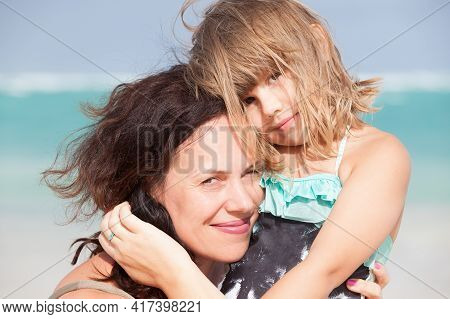 Smiling Young Caucasian Mother With Cute Little Daughter. Outdoor Portrait Photo Taken On The Beach