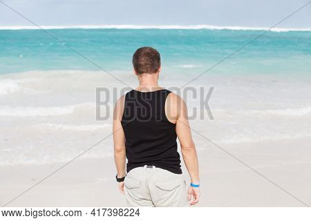 Young Adult Caucasian Man In Black Shirt Walk On The Beach In A Sunny Summer Day, Rear View. Dominic