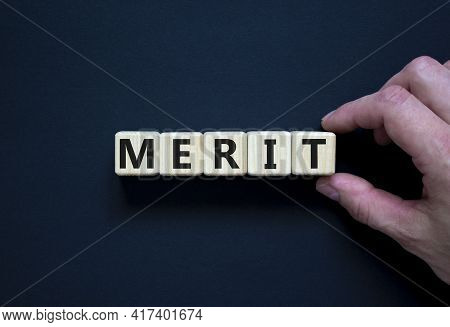 Merit Symbol. Wooden Cubes With The Word 'merit'. Businessman Hand. Beautiful Black Background, Copy