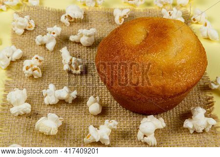 Orange Cake Surrounded By Popcorn Spread On The Table .
