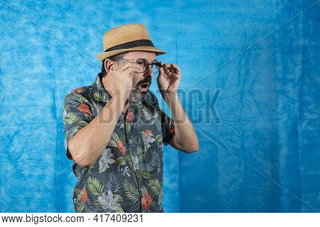 Person Dressed As A Tourist With A Printed Shirt And A Face Of Astonishment And Taking Off His Glass