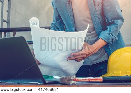 Engineer Holding Blueprint Working On Site Construction