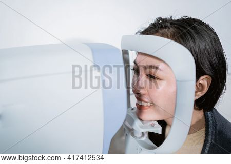 A Woman Is Undergoing An Examination Using An Eye Examiner Computer