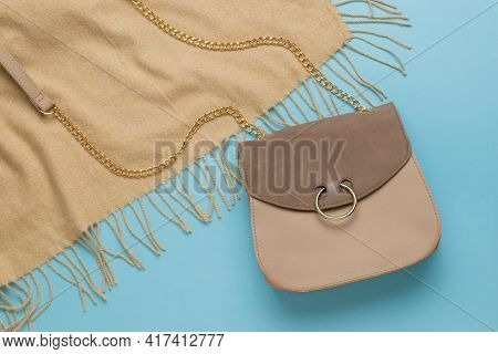 Beige Leather Bag And Beige Fabric On A Blue Background. A Fashionable Women's Accessory. Fashion Wo