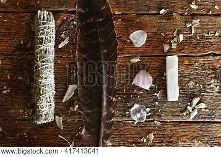 A Top View Image Of A White Sage Smudge Stick And Sacred Feather On A Dark Wooden Table Top.