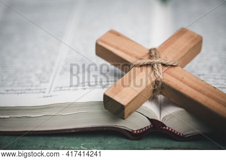 Closeup Of Simple Wooden Christian Cross  On Bible. Concept For Christian, Christianity, Catholic Re