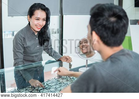 A Lady Shop Clerk Shows A Pair Of Glasses In A Window To A Customer