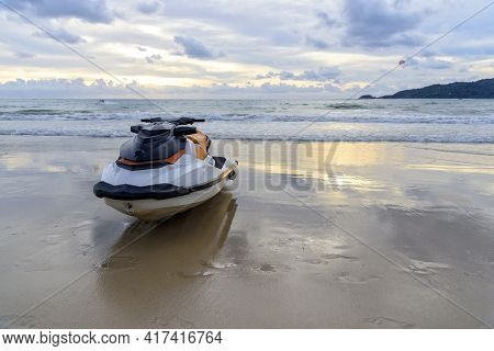 Jet Ski Or Water Scooter Parking On The Beach At Evening Time With Sunset Background.