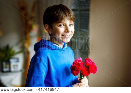 Beautiful Preteen Kid Boy Holding Bunch Of Clove Flowers. Happy Positive Child Congrats And Presents