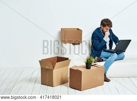 Business Man Sitting On The Couch With Laptop Boxes With Things Unpacking Office Official