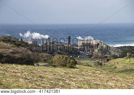 Sugar Mill On Coast Releasing Steam From Its Chimneys