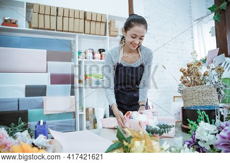 Young Woman Florist Working In Flower Shop Make Order Flannel Flower