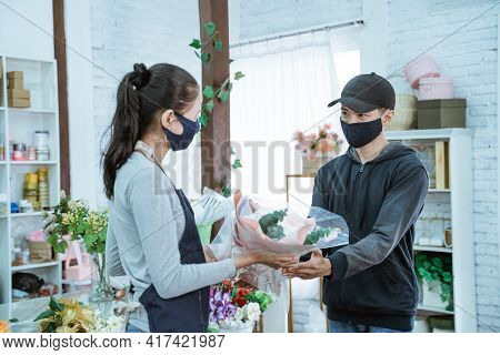 Young Female Shopkeeper Wearing A Face Mask And Apron. Servicing Male Flannel Flower Buyers