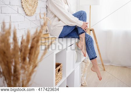 Home And Cosiness Concept - Young Slim Woman Sitting On Shelf In Living Room