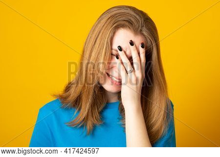 Disappointed Dejected Female Wearing Blue Loose T-shirt Covering Her Face With Hands Being Tired And