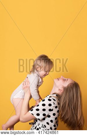 Sister Teenager With Baby Sister Smiling On A Yellow Background. Adorable Cheerful Sisters Of Differ