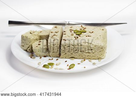 Halva Close-up On A White Plate On A White Background. Traditional Oriental Dessert Sweet Halva. Hal