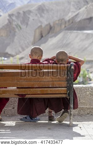 Two Young Buddhist Monk Resting On A Bench On A Sunny Day On The Street Next To The Mountain Monaste