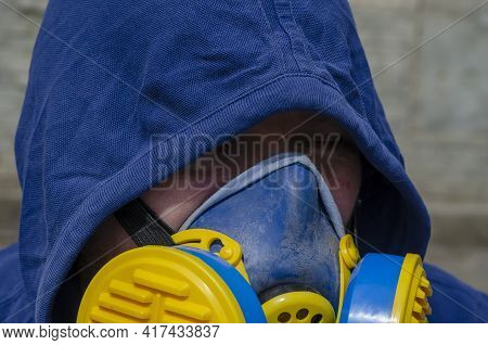 Portrait Of A Tired Adult Unrecognizable Man Wearing A Respirator And Wearing A Hood. A Middle-aged