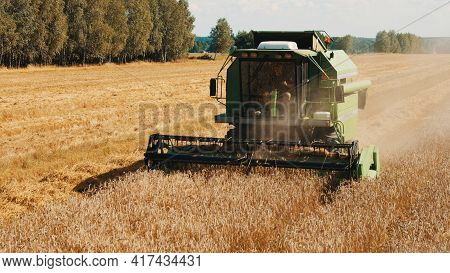 Warsaw, Poland 10.08.2020 - A Combine Harvester In The Golden Wheat Field. Farmer Driving The Harves