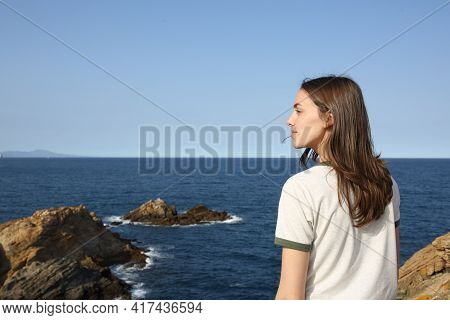 Casual Woman Standing Alone Contemplating Views On The Beach