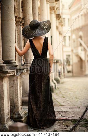 Fashion Woman Model In Hat Back Side View On Old City Street. Elegant Traveler Girl In Black Dress L