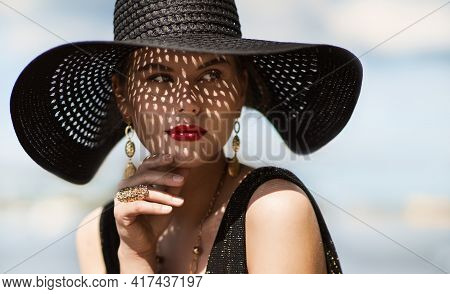 Woman In Hat Portrait. Fashion Luxury Model In Black Summer Hat With Make Up And Golden Jewelry. Clo