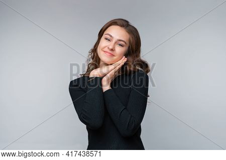 So Cute. Beautiful And Gently Young Brunette Woman Leans Her Face O Hands And Smiling, Gazing At Som