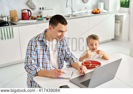 Busy Young Parent Father Working Or Learning From Home Office Using Laptop Computer Sitting At Kitch