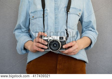 Close Up Of Cool Woman Wearing Casual Clothes Holding A Vintage Style Camera.isolated On Grey Backgr