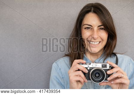 Front View Of Portrait Of Lovely Young Woman, Happy And Very Smiling, Holding A Retro Style Camera.c
