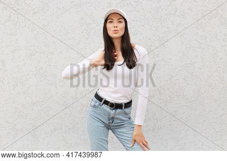Beautiful Dark Haired Female Wearing Stylish Clothing And Baseball Cap, Looking At Camera, Pouts Lip