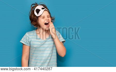 Photo Of Adorable Sweet Kid Nightwear Yawning Stretch. Sleepy Child Girl Isolated On Blue Background
