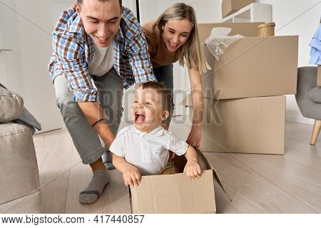 Happy Parents Having Fun Playing With Cute Toddler Kid Son Riding In Box On Moving Day. Excited Youn