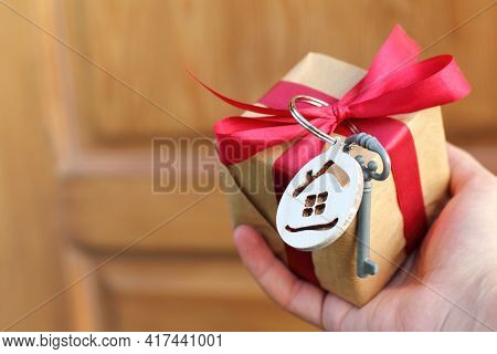 Hand With A Gift Decorated With A Small House And A Key On The Background Of The Door. Real Estate O