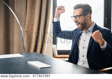 Enthusiastic Unshaved European Business Man Sits In Front Of A Computer At Desk And Cheering, Scream